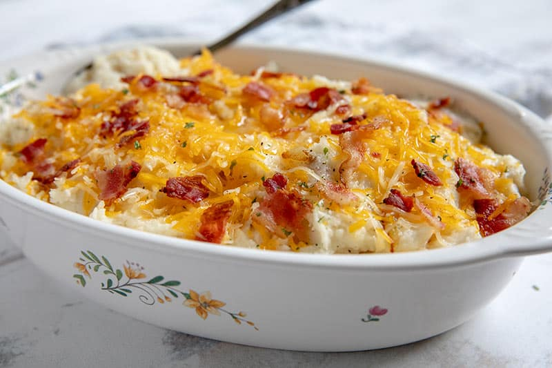 These creamy Caramelized Onion Mashed Potatoes are loaded with flavor and topped with butter, cheese, and bacon.