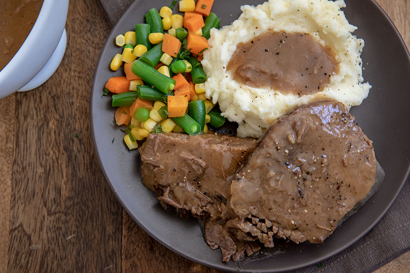 Round steak in gravy with mashed potatoes and colorful vegetables.
