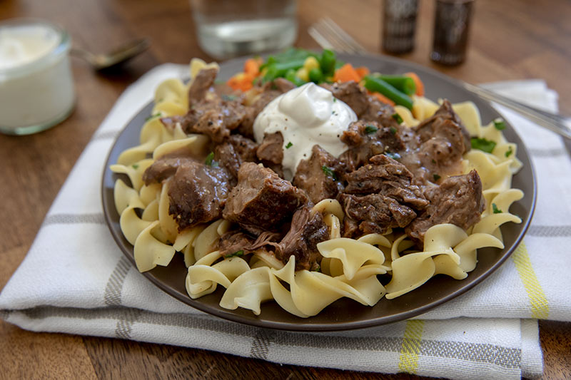 Beef and gravy over noodles topped with a dollop of sour cream.