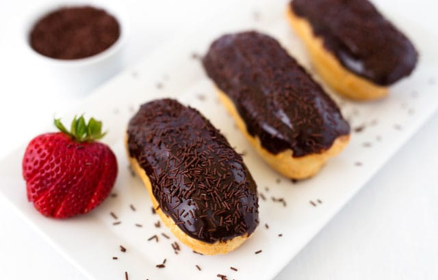 Chocolate Eclairs are made by filling a crisp, buttery eclair shell with a light, creamy vanilla pastry cream and glazing it with a rich, chocolate icing.