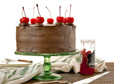 Side view of a fully baked and decorated old-fashioned chocolate cake with cherry filling, glossy chocolate icing and maraschino cherries on top, next to a jar of cherries and a green and white striped cloth.
