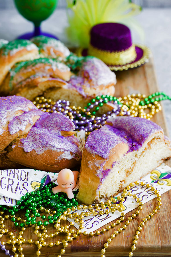 Sliced Mardi Gras King Cake with gold, green and purple beads