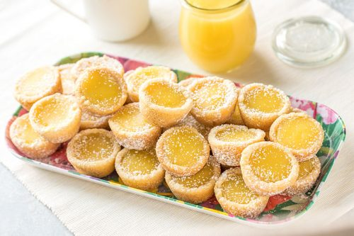 serving dish of several bright yellow lemon bar cookie cups