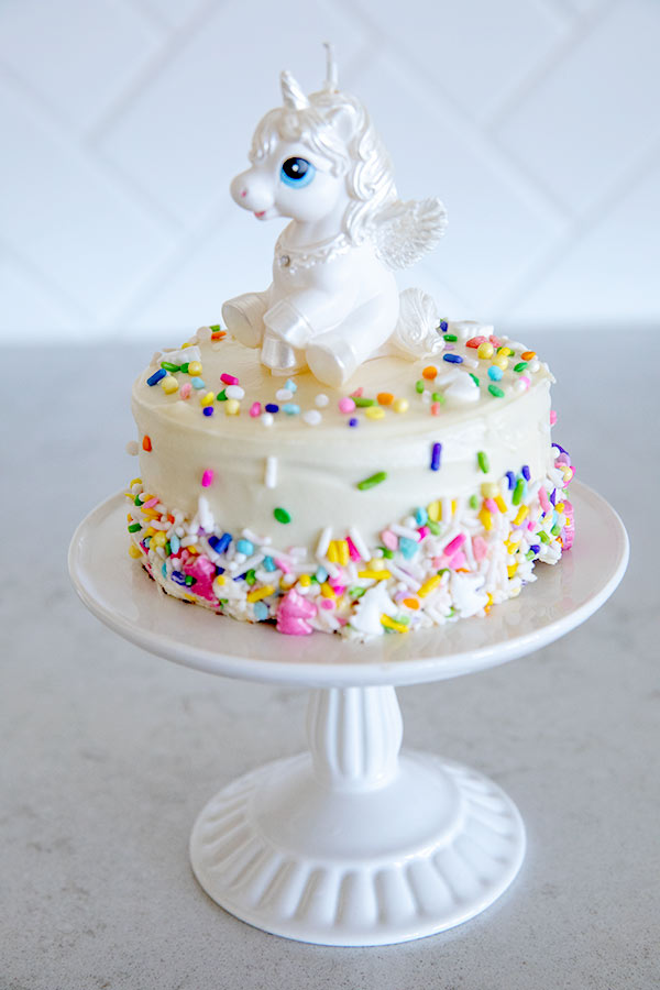 Colorful sprinkles on a chocolate smash cake topped with an adorable unicorn candle