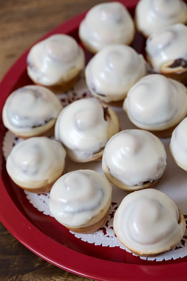 These Cinna-Mini Cinnamon Rolls are a classic ooey, gooey cinnamon roll topped with a rich cream cheese frosting in a fun mini size perfect for a party. Betcha can't eat just one.