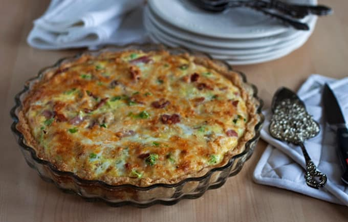 quiche in a pan with serving utensils and stacked plates