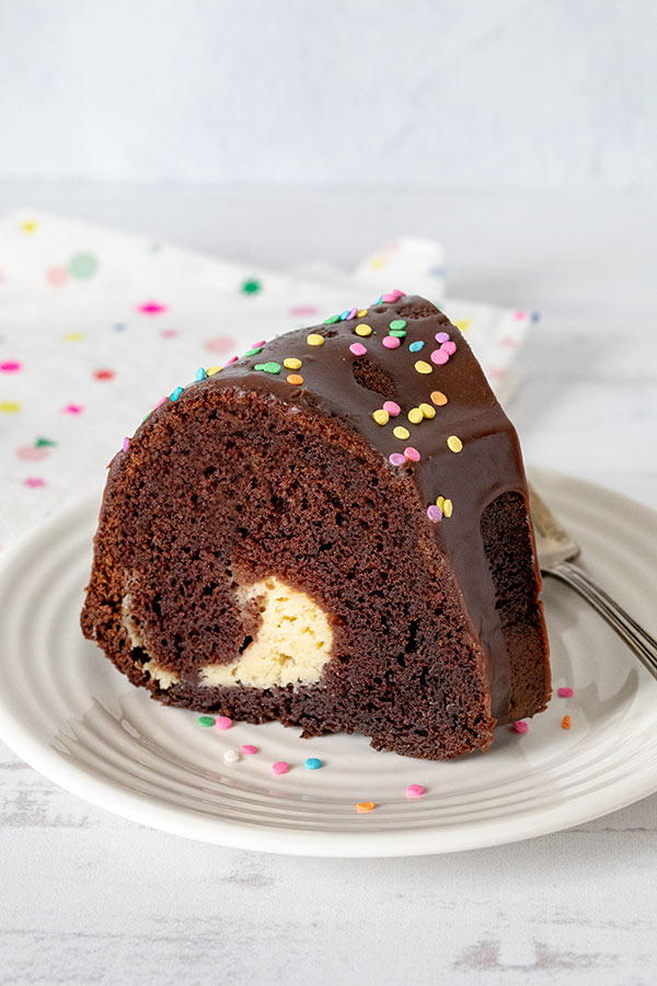 Chocolate Bundt Cake with a Cream Cheese Swirl sliced on a plate.