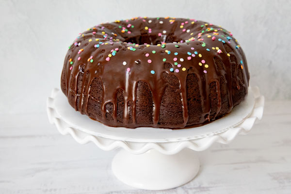 A chocolate bundt cake on a cake stand with chocolate icing and colorful sprinkles.