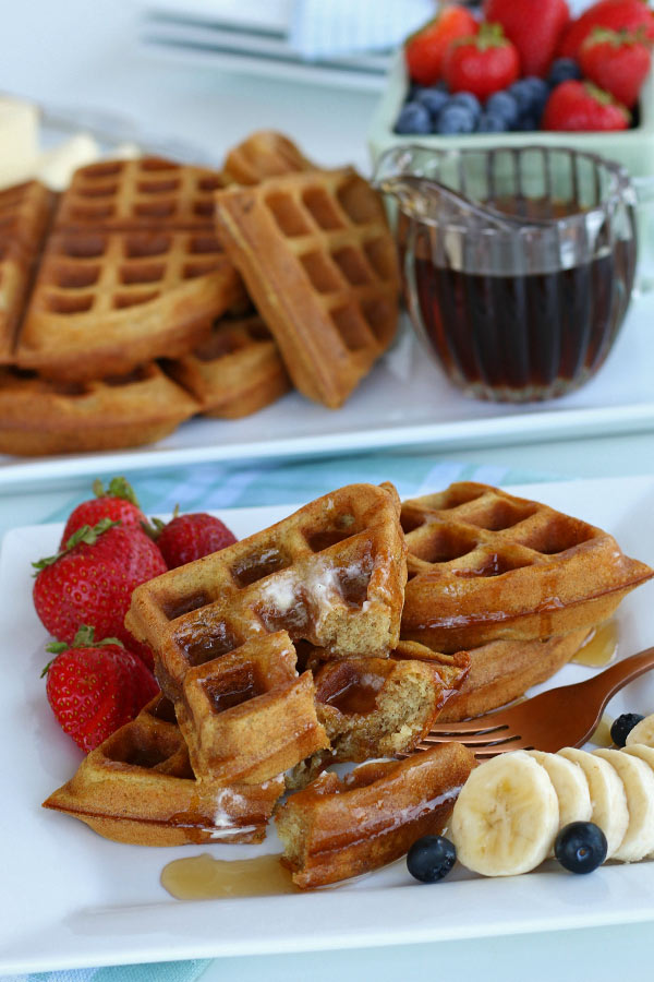 Whole wheat waffle recipe finished and plated with fruit and syrup.