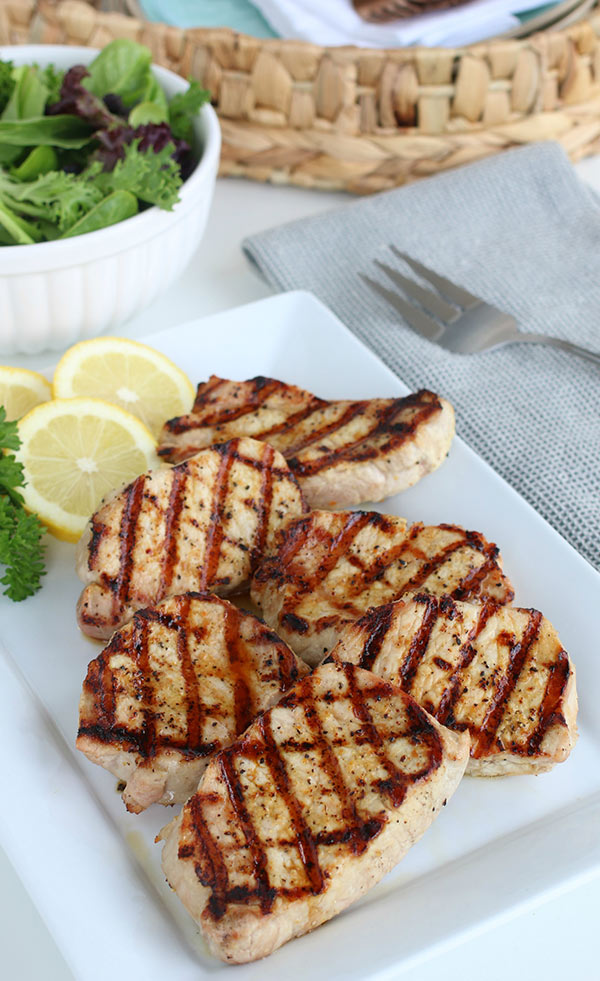 A platter of Easy Grilled Lemon Pepper Pork Chops with Lemon and Parsley