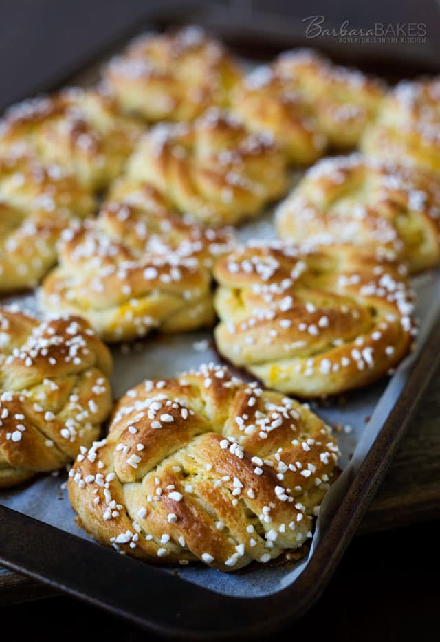 Swedish Orange Sweet Buns made with a buttery, cardamom dough layered with fragrant orange sugar, then knotted, topped with Swedish pearl sugar and baked until they're golden brown.