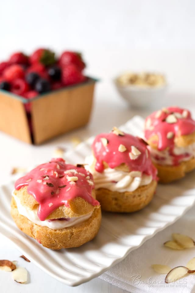 A crisp, buttery cream puff shell filled with a no-bake raspberry cheesecake filling and drizzled with a tart triple berry icing.