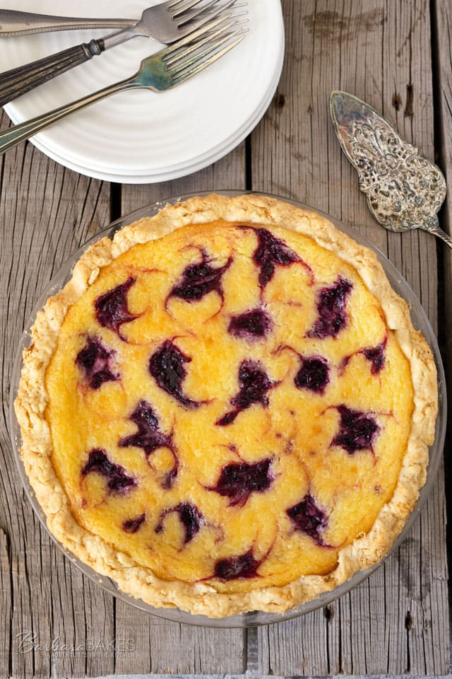 A tart Lemon Blackberry Chess Pie with a bright lemon flavor, a layer of blackberries on the bottom and dollops of blackberries swirled on top.