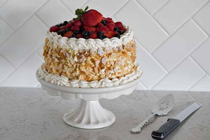 A luscious Triple Berry Choux Cake with four layers of choux sandwiched with berry cream, iced with vanilla bean cream, and topped with fresh berries.