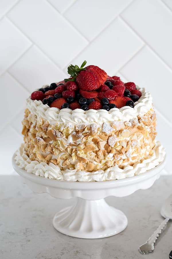 A luscious Triple Berry Choux Cake with four layers of choux sandwiched with triple berry cream, iced with vanilla bean whipped cream, and decorated with choux crumbs, powdered sugar and fresh berries. A special dessert for any occasion.