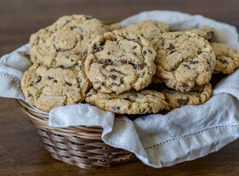 A basket of cookies with a tan linen napkin in the basket