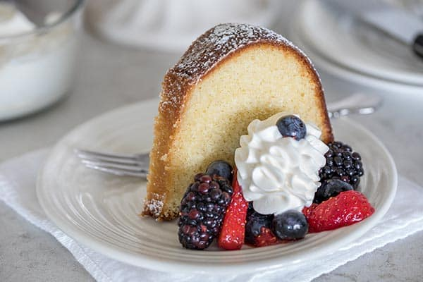 High Altitude Classic Vanilla Bundt Cake served with berries and cream.