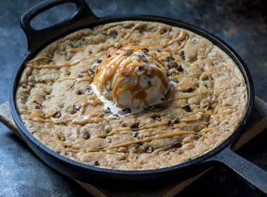 Caramel Stuffed Chocolate Chip Skillet Cookie topped with vanilla ice cream and caramel sauce