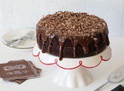 A Triple Chocolate Layer Cake drizzle with rich milk chocolate ganache and topped with shaved chocolate curls.