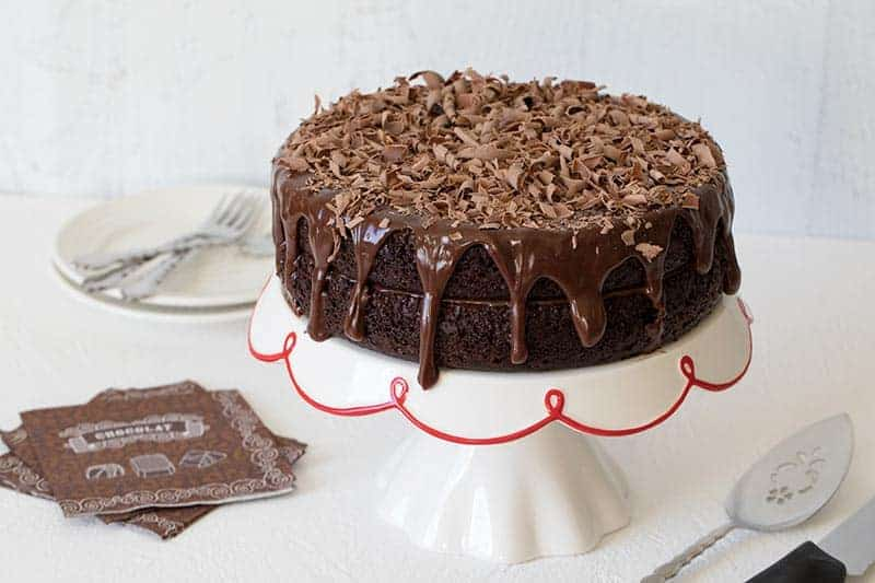 A Triple Chocolate Layer Cake drizzled with rich milk chocolate ganache and topped with shaved chocolate curls.