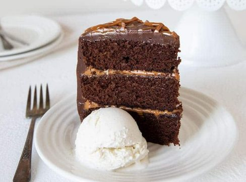 Chocolate Dulce De Leche Triple Layer Cake on a white plate with a scoop of ice cream and a fork