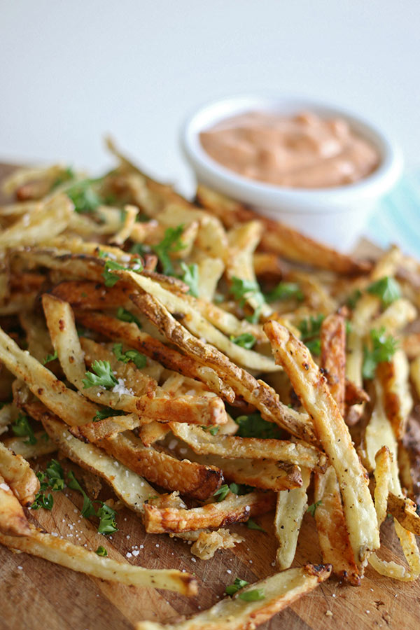 Seasoned French fries with fry sauce in the background