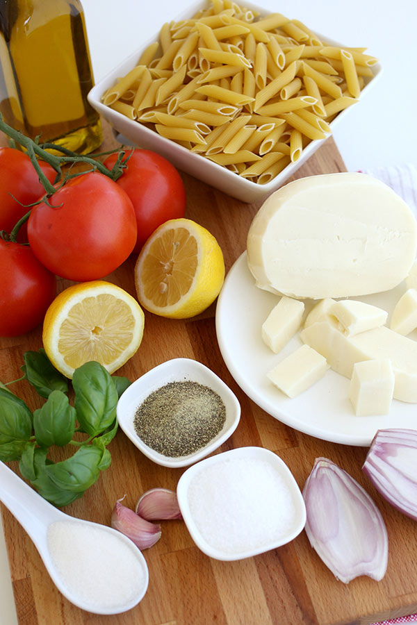 Ingredients to make Pasta Caprese Salad, including pasta, tomatoes and mozzarella cheese