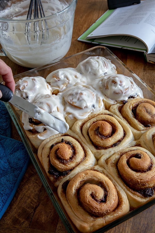 Icing a pan of just baked Easy Homemade Cinnamon Rolls