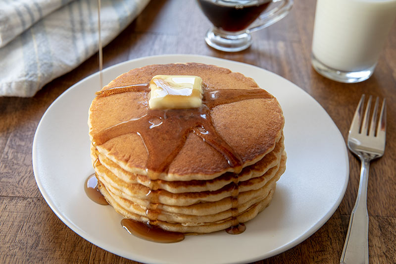 A stack of sourdough pancakes with maple syrup dripping down.