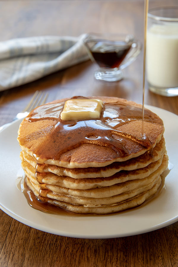 A stack of six sourdough pancakes drizzled with maple syrup.