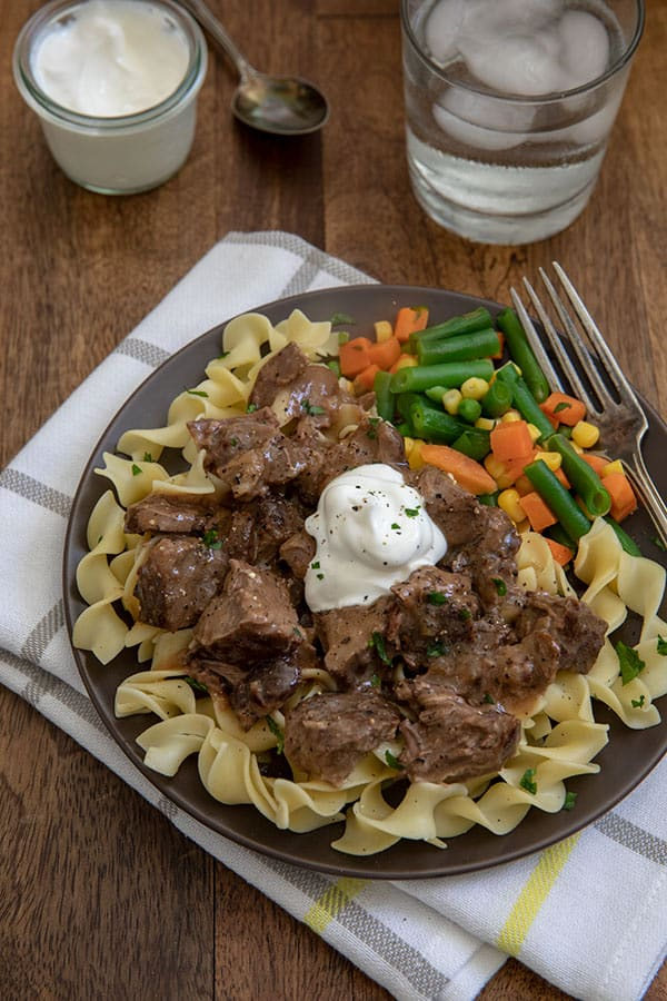 Round steak in gravy on top of a bed of noodles with a dollop of sour cream