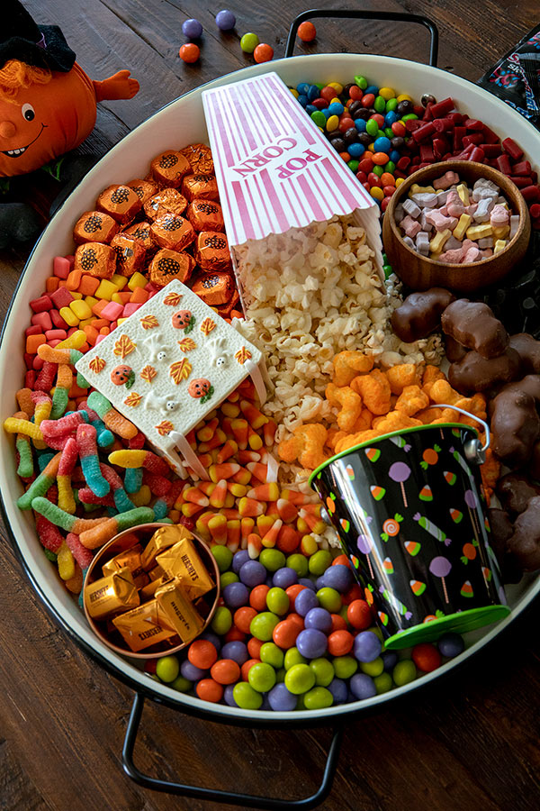Fun Halloween Movie Board with Caramel M&M's in fun Halloween colors, Dove Milk Chocolate Pumpkins; candies, Reese's Peanut Butter Bats, Hershey's Nuggets,Trolli Sour Worms, Skittles, Starburst, and SweetTart Skulls and Bones.