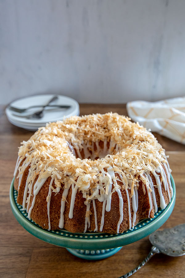 Coconut Bundt Cake on a blue cake stand with plates and forks
