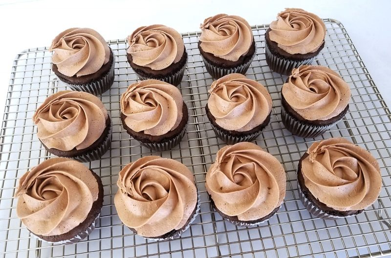 Nutella buttercream piped in a rosette pattern on chocolate cupcakes