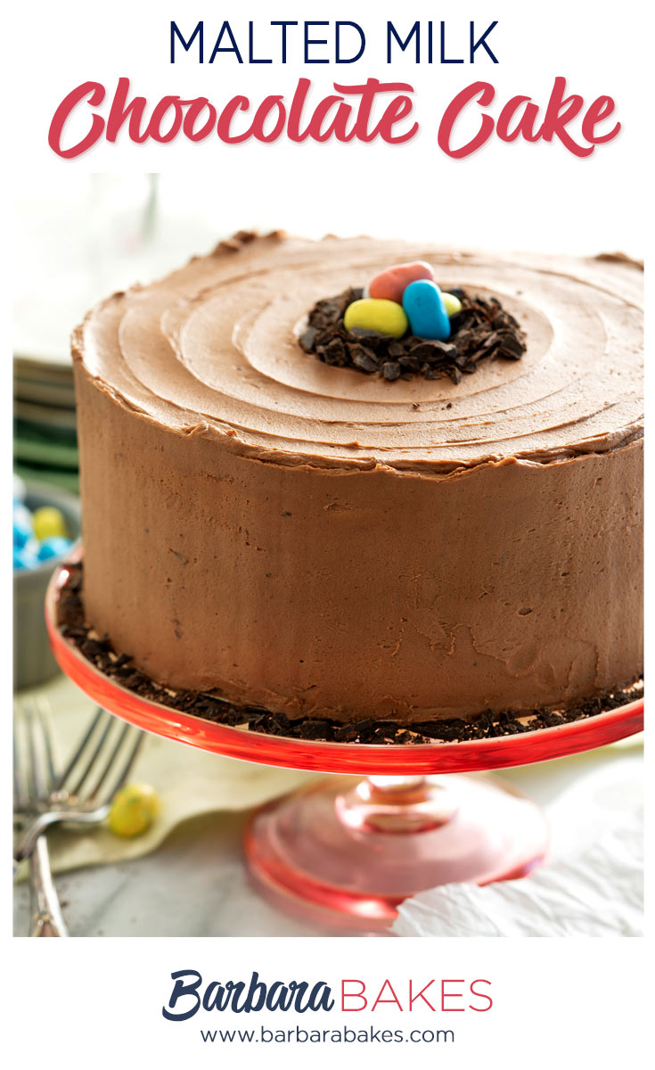 Malted milk chocolate layer cake on a red cake stand frosted in smooth fluffy homemade chocolate frosting and decorated with colorful candy.