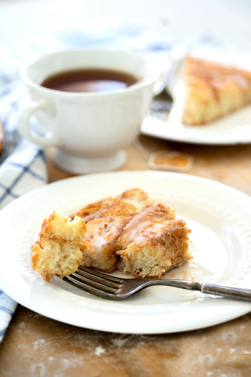 Close up on a white plate with a slice of cinnamon roll coffee cake with cinnamon sugar coating and simple sugar glaze eaten with a metal fork and a cup of coffee in the background.