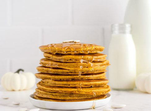 stack of fluffy pumpkin pancakes on a white plate with a white pumpkin and milk jars in the background